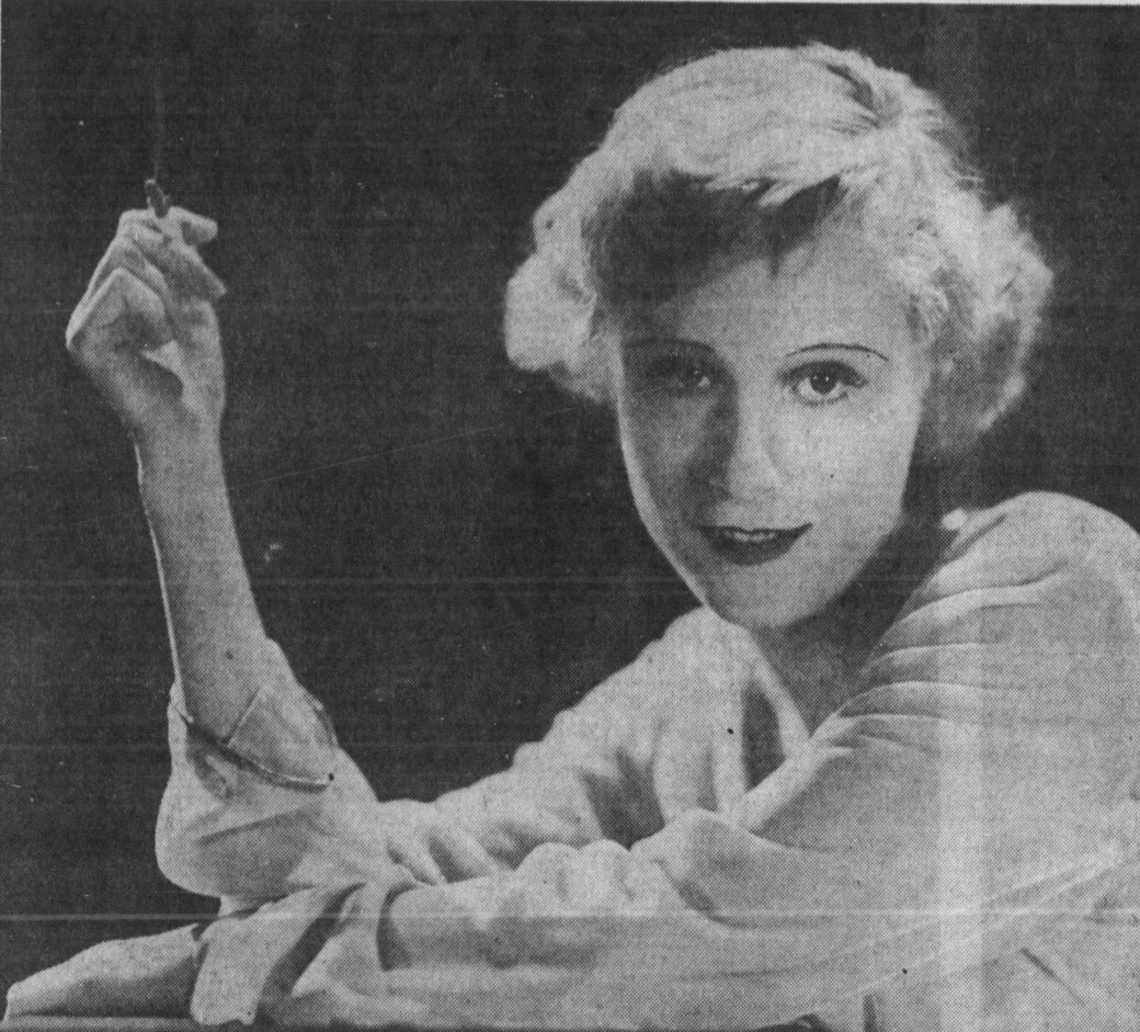 Peg Entwistle, a blonde woman with shot hair curled at the sides, leans on a surface with her arms on it, holds a smoking cigarette in a raised arm. She looks directly into the camera, iling.